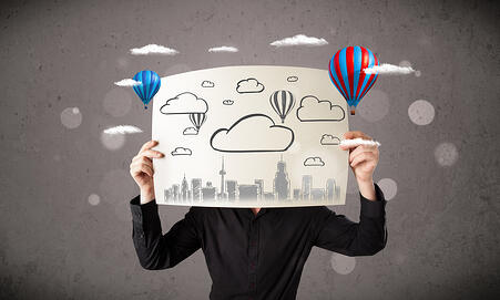 Businessman holding a cardboard in front of his head with cityscape and ballons drawing-1