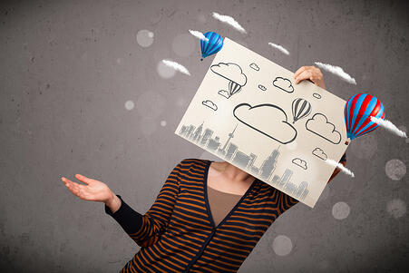Woman holding a cardboard in front of her head with cityscape and ballons drawing